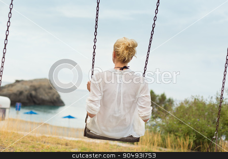 Young blonde woman sitting on the swing stock photo, Young blonde woman sitting on the swing on beach. by kasto