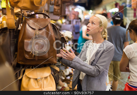 Casual blond woman shopping for leather bag. stock photo, Beautiful casually dressed caucasian blond woman shopping for new leather bag on crafts market in Chania, Crete, Greece. by kasto
