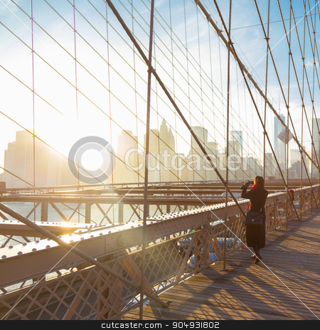 Brooklyn bridge at sunset, New York City. stock photo, Woman taking a photo from Brooklyn bridge. New York City Manhattan downtown skyline in sunset with skyscrapers illuminated over East River panorama as seen from Brooklyn bridge. by kasto