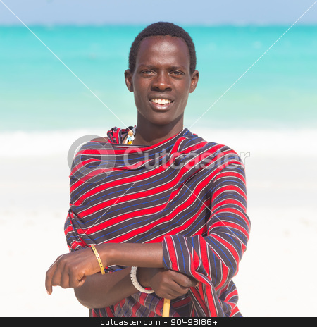 Traditonaly dressed black man on beach.  stock photo, Traditonaly dressed black man on the beach. Maasai warrior on picture perfect tropical sandy beach on Zanzibar, Tanzania, East Africa. by kasto
