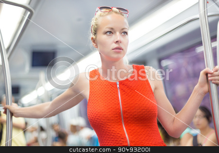 Lady traveling by metro. stock photo, Beautiful blonde caucasian lady in red dress traveling by metro. by kasto