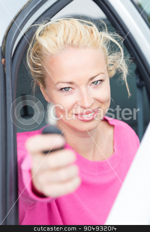 Woman driver showing car keys. stock photo, Woman driver showing car keys. Young female driving happy about her new car or drivers license. Caucasian model. by kasto