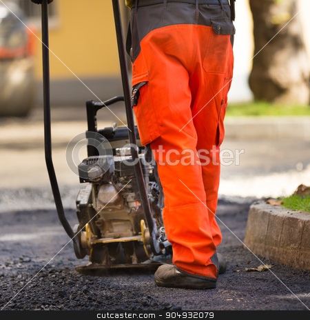 Asphalt surfacing manual labor. stock photo, Construction workers during asphalting road works wearing coveralls. Manual labor on construction site. by kasto
