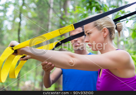 Training with fitness straps outdoors. stock photo, Young active people does suspension training with fitness straps outdoors in the nature. by kasto