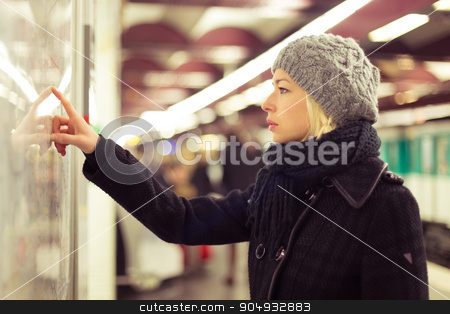 Lady looking on public transport map panel. stock photo, Casually dressed woman wearing winter coat, orientating herself with public transport map panel, pointing on her final destination. Urban transport. by kasto