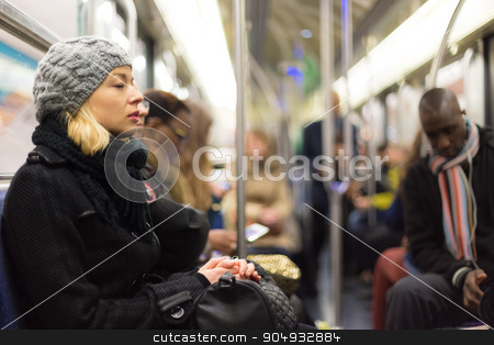 Woman napping on subway full of people. stock photo, Beautiful blonde caucasian lady, wearing winter coat, napping while traveling by metro in rush hour. Public transport. by kasto