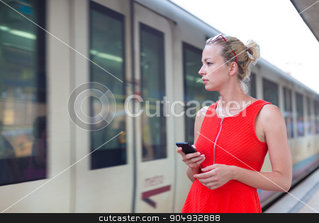 Young woman on platform of railway station. stock photo, Young woman in red dress with a cell phone in her hand waiting on the platform of a railway station for their train. to arrive. by kasto