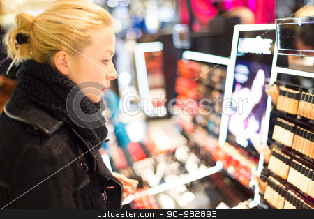 Beautiful woman shopping in beauty store. stock photo, Beautiful blond lady testing  and buying cosmetics in a beauty store. by kasto
