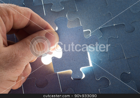 Man holding puzzle piece stock photo, Man putting puzzle piece, close up view by cherezoff