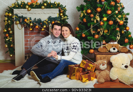 Nice love couple sitting on carpet in front of fireplace stock photo, Nice love couple sitting on carpet in front of fireplace. Woman and man celebrating Christmas by zakharovaleksey
