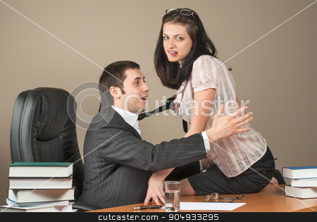 Businesswoman is seducing her boss at office stock photo, Flirting in the office as a beautiful dark-haired businesswoman pulls a colleague towards her by his tie by Aikon