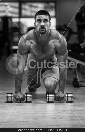 Push Ups With Dumbbels stock photo, Young Athlete Doing Pushups With Dumbbells As Part Of Bodybuilding Training by Jasminko Ibrakovic