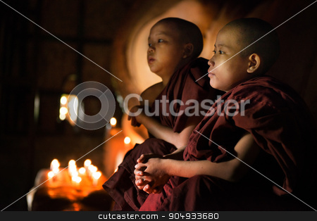Buddhist novices praying inside temple stock photo, Young novice monks sitting inside a Buddhist temple, Bagan, Myanmar. by szefei