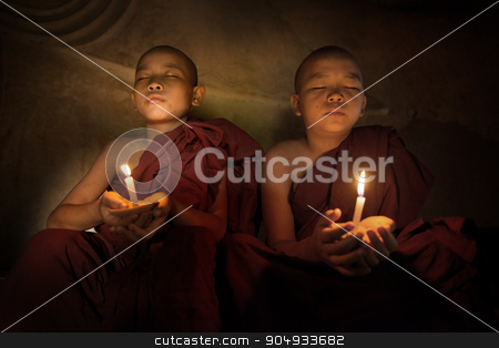 Buddhist novices praying with candlelight stock photo, Little monks praying with candlelight by szefei