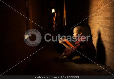 Buddhist novice reading stock photo, Young Buddhist novice monk reading book inside monastery, natural light shining thru. by szefei