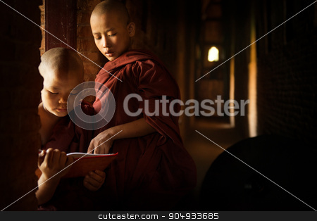 Buddhist novices learning inside temple stock photo, Young Buddhist novice monk reading in monastery with beautiful natural sunlight from window. Buddhist teaching, Myanmar. by szefei