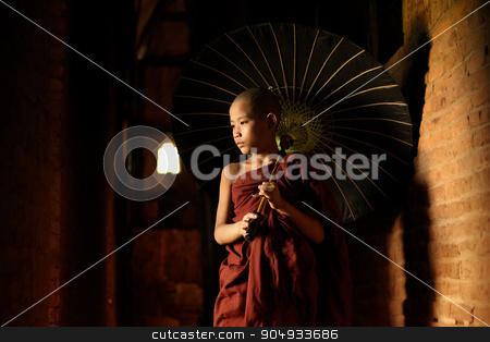 Buddhist novice walking with umbrella stock photo, Young novice monks walking thru a Buddhist temple, Bagan, Myanmar. by szefei