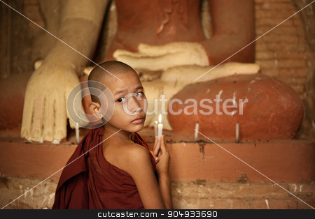 Buddhist novices lighting up candlelight in temple stock photo, Portrait of young novice monk praying with candle light inside a Buddhist temple, Bagan, Myanmar. by szefei