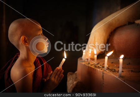 Buddhist novices praying with candlelight in temple stock photo, Portrait of young novice monk praying with candlelight inside a Buddhist temple, low light setting, Bagan, Myanmar. by szefei