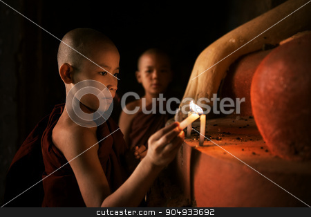 Buddhist novices praying with candlelight in monastery  stock photo, Portrait of young novice monks lighting up candlelight inside a Buddhist temple, low light setting, Bagan, Myanmar. by szefei