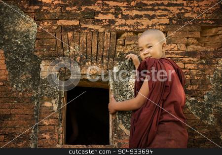Buddhist novice monk stock photo, Young novice monk standing outside Buddhist temple, Bagan, Myanmar. by szefei