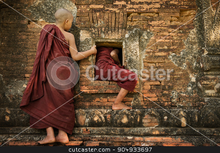 Playful young novice monks stock photo, Two playful young novice monks climbing into Buddhist temple from window, Bagan, Myanmar. by szefei