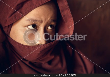 Buddhist novice monk covered with robe stock photo, Portrait of young novice monk inside Buddhist temple, low light with noise setting, Bagan, Myanmar. by szefei