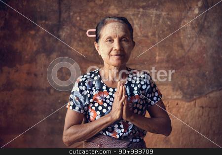 Old Burmese woman stock photo, Portrait of traditional Asian Burmese woman praying, standing inside a temple, low light, Bagan, Myanmar by szefei