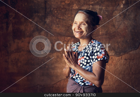 Old Burmese woman stock photo, Portrait of traditional Asian Burmese woman greeting, standing inside a temple, low light, Bagan, Myanmar by szefei