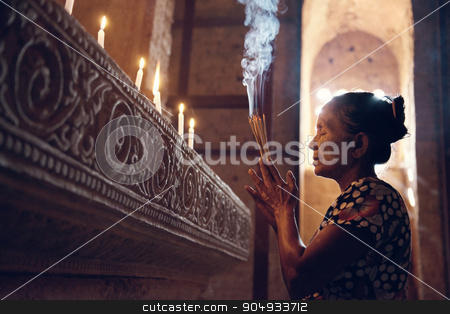 Old Burmese woman stock photo, Old wrinkled traditional Asian woman praying with incense sticks inside a temple, low light, Myanmar by szefei
