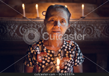 Old Burmese woman stock photo, Old wrinkled traditional Asian woman praying with candle light inside a temple, low light, Myanmar by szefei