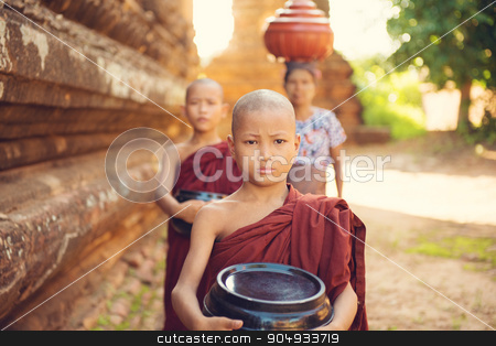 Buddhist novice monks collecting foods stock photo, Southeast Asian young Buddhist monks walking morning alms in Old Bagan, Myanmar by szefei