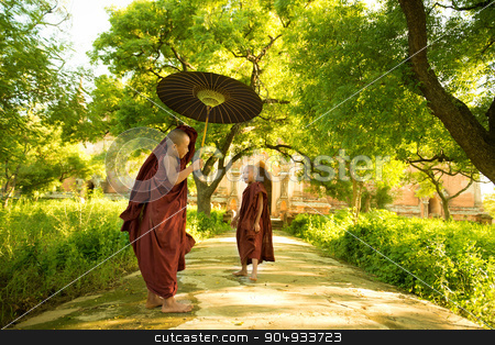 Young Buddhist novice monks stock photo, Two little Buddhist novice monks walking outdoors under shade of green tree, outside monastery, Myanmar. by szefei