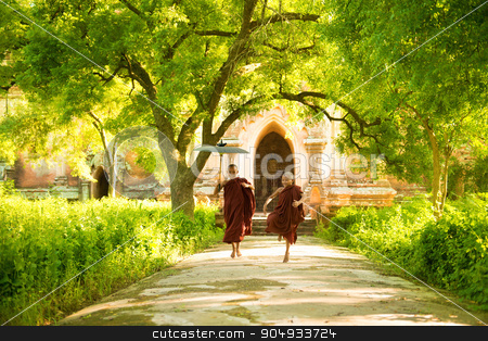 Young Buddhist novice monks running stock photo, Two little Buddhist novice monks running outdoors under shade of green tree, outside monastery, Myanmar. by szefei