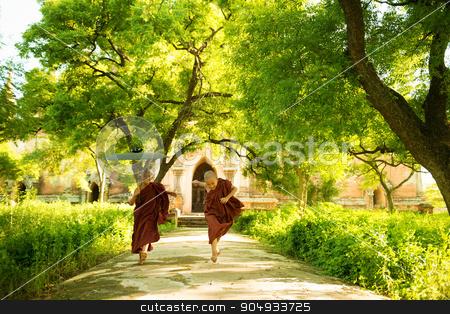 Young Buddhist novice monks running outside monastery stock photo, Two little playful Buddhist novice monks running outdoors under shade of green tree, outside monastery, Myanmar. by szefei
