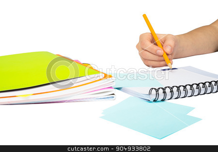 Females hand writing in notebook stock photo, Females hand writing in notebook on isolated white background, closeup by cherezoff