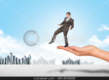 Businessman walking from edge of hand stock photo, Businessman walking from edge of hand with city view background by cherezoff