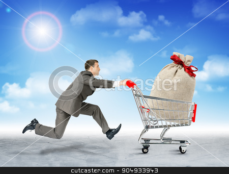 Running businessman with bag in shopping cart stock photo, Running businessman with big bag in shopping cart by cherezoff