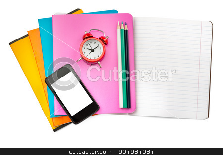 Open notebook with set of crayons and smartphone stock photo, Open notebook with smartphone and alarm clock on isolated white background by cherezoff
