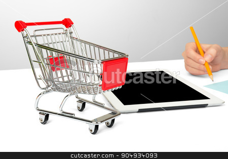 Females hand using tablet stock photo, Females hand using tablet isolated on white background with shopping cart by cherezoff