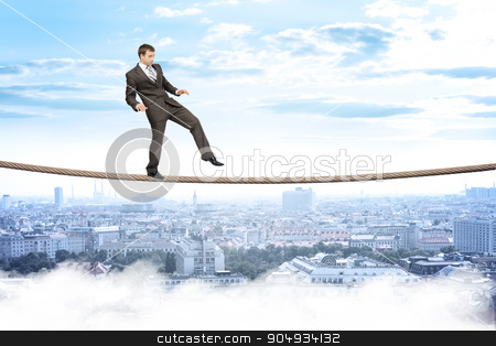 Businessman gently walking on rope stock photo, Businessman gently walking on rope above city with closed eyes by cherezoff