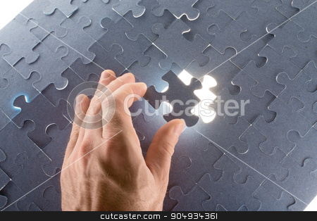 Man holding puzzle piece stock photo, Man holding puzzle piece making puzzle, close up view by cherezoff