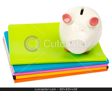 Piggy bank on pile of copybooks stock photo, Piggy bank on pile of copybooks on isolated white background, side view by cherezoff