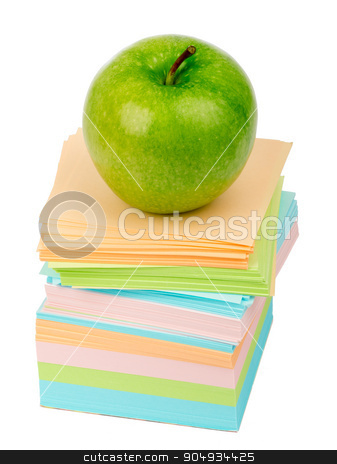 Fresh green apple on pile of stickers stock photo, Fresh green apple on pile of stickers on isolated white background by cherezoff
