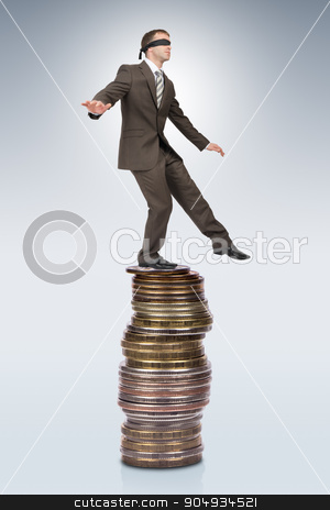 Businessman walking from edge of coins pile stock photo, Businessman walking from edge of coins pile on grey background by cherezoff