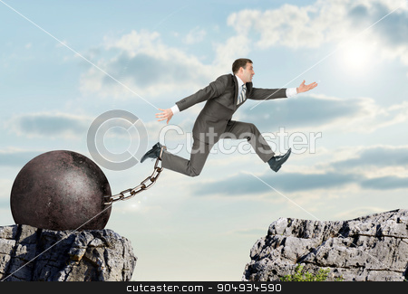 Image of young businessman jumping over gap stock photo, Image of young businessman with iron ballast jumping over gap by cherezoff