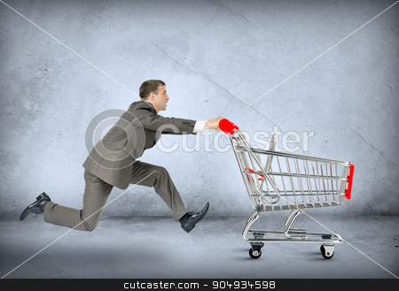 Businessman pushing empty shopping cart  stock photo, Businessman pushing shopping cart on grey wall background by cherezoff