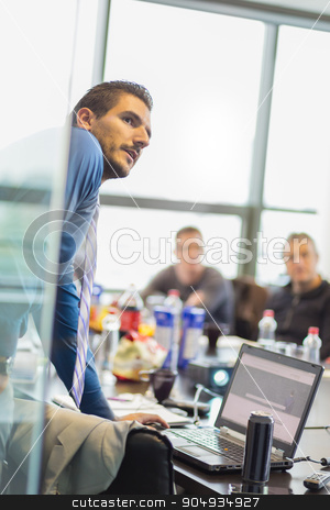 Business presentation on corporate meeting. stock photo, Business man making a presentation at office. Business executive delivering a presentation to his colleagues during meeting or in-house business training, explaining business plans to his employees. by kasto