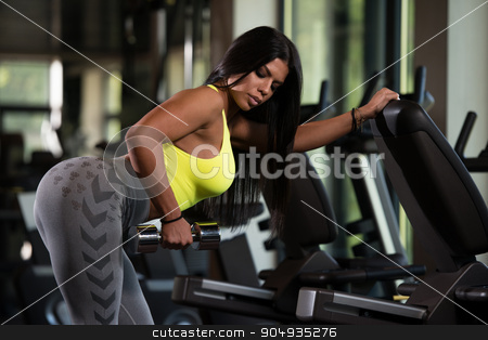 Latino Woman Doing Exercise For Back stock photo, Sexy Mexican Woman Working Out Back With Dumbell In Fitness Center by Jasminko Ibrakovic