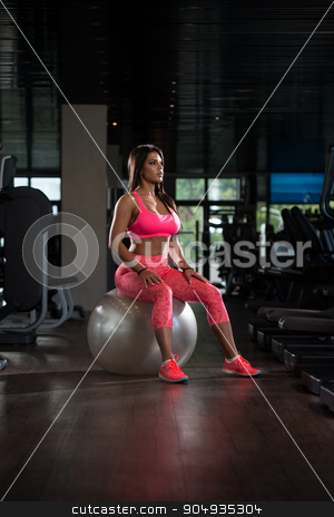 Sexy Latino Woman Resting After Workout In Gym stock photo, Young Mexican Woman Resting On Ball After Working Out In Fitness Cente by Jasminko Ibrakovic